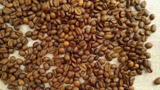 Aromatické kávová zrna jsou náhodně roztroušeny na textilní ubrousek, v pomalé rotaci