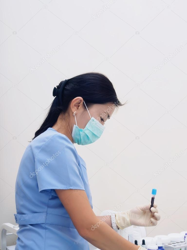 Asian nurse drawing blood to prepare examination in laboratory