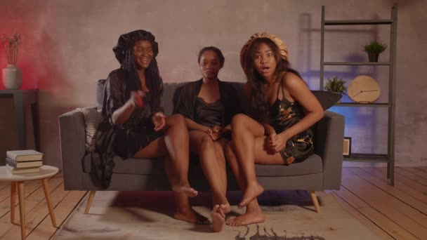 Három afro-amerikai lány ül a kanapén TV-t nézve és nevet.