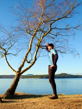 Runner in blue shirt and black leggins along tree at coastline. Sport and healthy lifestyle concept