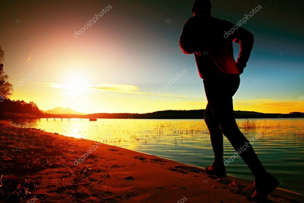 Sportsman running at amazing summer sunset along coastline in sport and healthy life  style