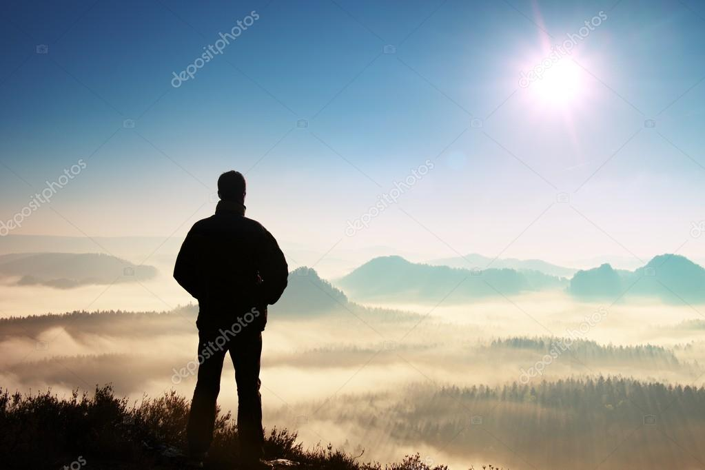 Man stands on cliff of sandstone rock and watching over misty valley to Sun. Beautiful moment