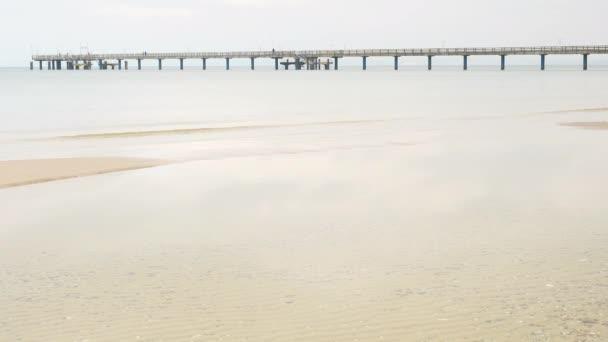Die lange Seebrücke oder Seebrücke über ruhiger See gegen launischen Himmel. Ostseestrand mit Groynes bei trübem Wetter.