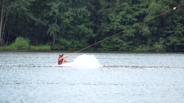 Straz, Czechia - 29th of July 2021.  Wakeboarding girl falling and diving into water of lake.