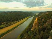 podzimní ranní na skalách nad velké řeky, čerstvý modrý mrak na obloze, světla ve městě na březích řeky. zelené lesy v krajině, svítání na obzoru