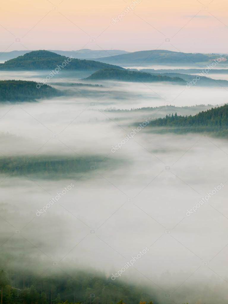 Autumn misty landscape. Dreamy atmosphere, the fog is shaking between peaks of hills. Chilly dreamy autumn morning in Bohemian Switzerland park.