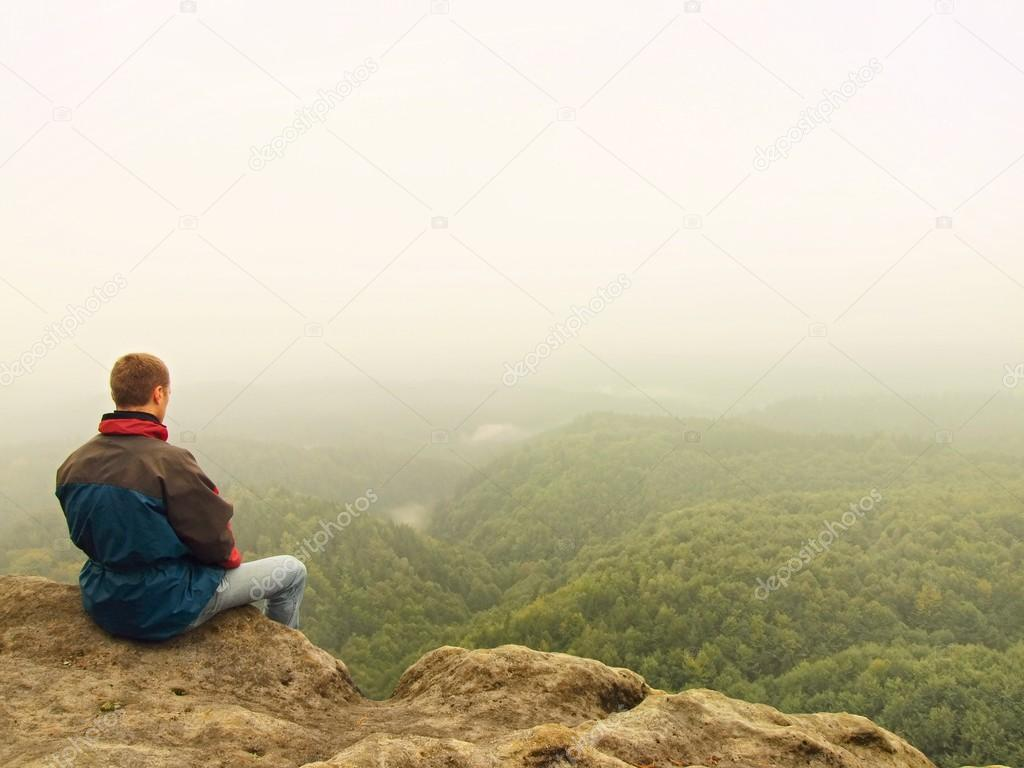 Sad Man Sit On The Peak Of Sandstone Rock And Watching Over