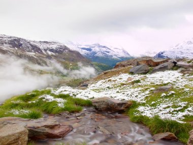 First snow in Alps touristic region. Fresh green meadow with rapids stream. Peaks of Alps mountains in background. Foamy water is running down over slipper stones in snowy green meadow.