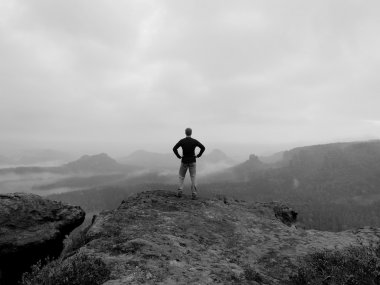 Tourist is standing on the peak of sandstone rock in rocky park and watching over the morning misty valley to big Sun. Black and white photo.