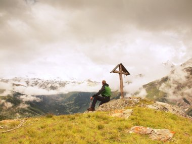 Tourist stand on rocky view point and watching into misty Alpine valley. Wooden cross at a mountain peak. Cross on top of a mountain peak as typical in the Alps.