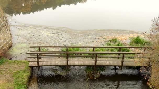 Studené vody zápach proud toku pod malého jezu pod dřevěným mostem. Přírodní weir vlnky strašlivý zápach vody