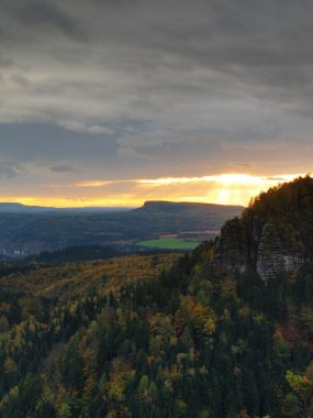 Autumn sunset view over sandstone rocks to fall colorful  valley of Bohemian Switzerland. Sandstone peaks and hills increased from colorful background.