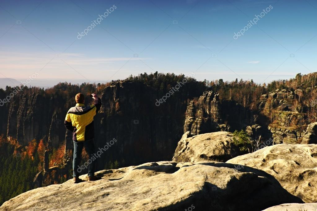 Man is taking photos on peak in rock empires park and watching over autumn misty valley. Sunny fall day.