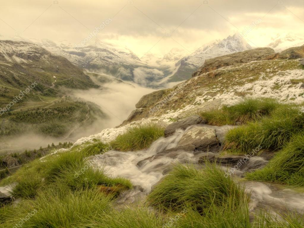 Brook in fresh green Alps meadow, snowy peaks of Alps in background. Cold misty and rainy weather in mountains at the end of summer.