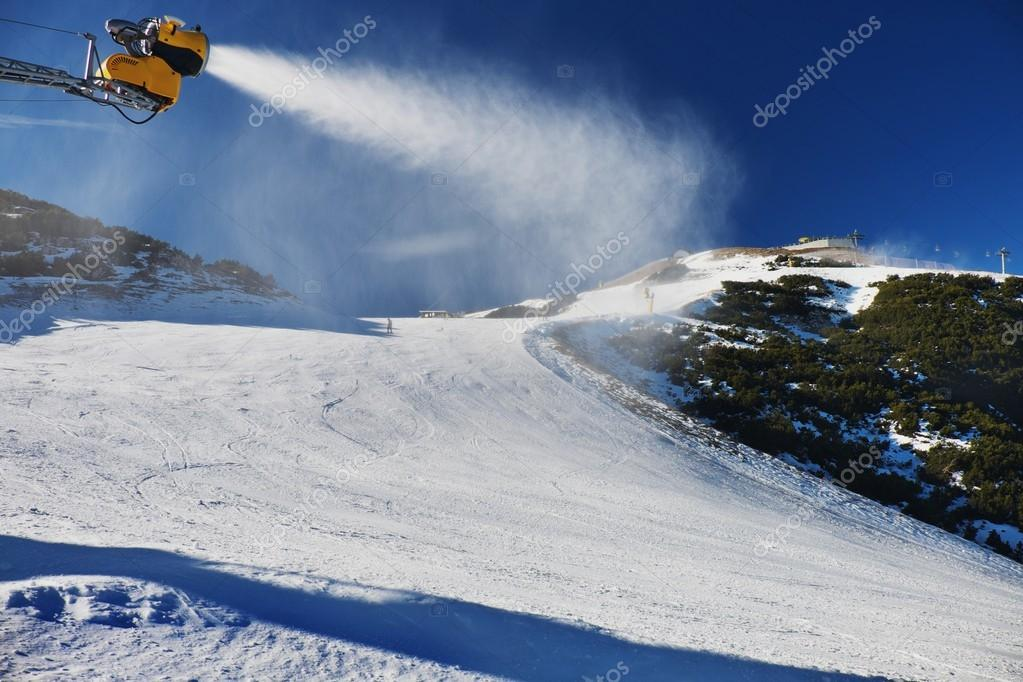Snow making on slope. Skier near a snow cannon making fresh powder snow. Mountain ski resort and winter calm mountain landscape.