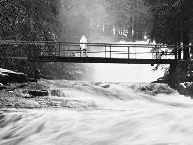 Man on bridge above troubled water. Huge stream of rushing water masses below small footbridge. Fear of floods.