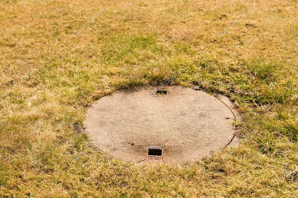 Concrete manhole cover drainage system in the midst of cropped dry grass