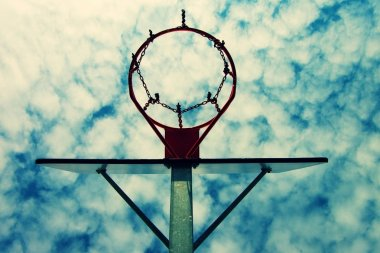 Old neglect basketball backboard with rusty hoop above street court. Blue cloudy sky in bckground. Retro filter