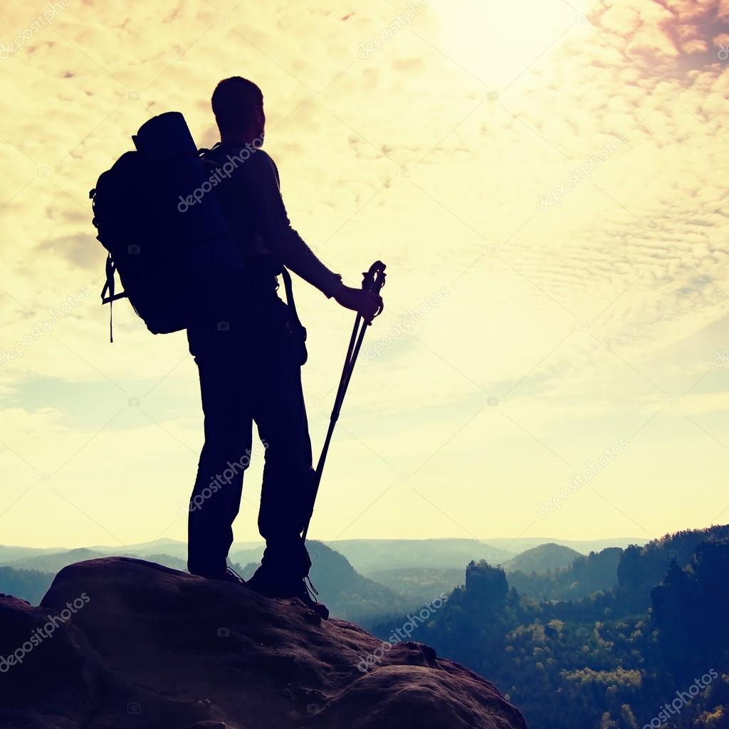 Silhouette of hiker with big backpack and poles in hands. Sunny colorful daybreak in rocky mountains. Man stand on rocky view point above misty valley.