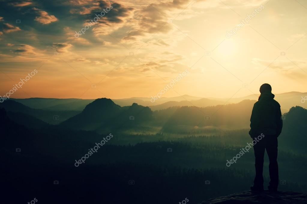 Silhouette of young tourist with hands in pockets. Sunny spring daybreak in rocky mountains. Girl stand on rocky view point above misty valley. Painting effect.