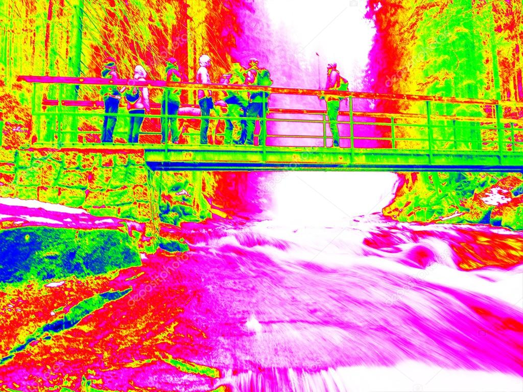 Foamy water of waterfall, bellow footpath bridge with people. Cold water of mountain river in infrared photo. Amazing thermography.