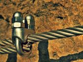 Detail der Chromschrauben Karabinerhaken und Ösen am und am Seil. Eisen verdreht Seil durch Schrauben Karabinerhaken miteinander verbunden. Detail der am Sandsteinfelsen verankerten Seilenden