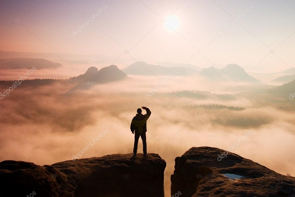 Beautiful moment the miracle of nature. Man stands on the peak of sandstone rock in national park Saxony Switzerland and watching over the misty and foggy morning valley to Sun.