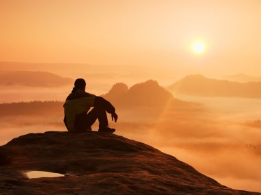 Spring landscape. Hiker in black on the rocky peak. Wonderful daybreak in mountains, heavy orange mist in deep valley. Man sit on the rock and watch over the fog to miracle of nature