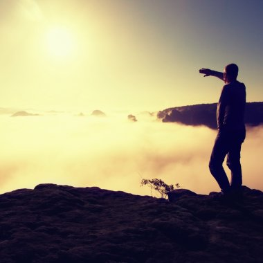 Man in shirt and jeans is standing on the peak of sandstone empire  and watching over the misty and foggy morning valley to Sun. Beautiful moment the miracle of nature