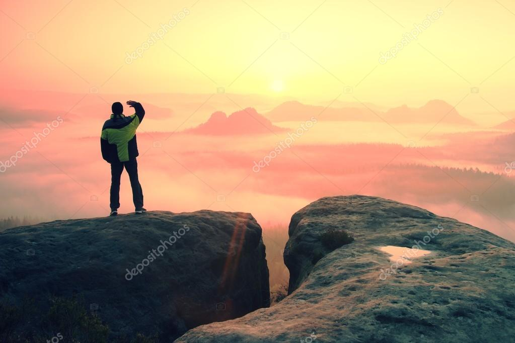 Moment of loneliness. Man on the rock empires  and watch over the misty and foggy morning valley to Sun