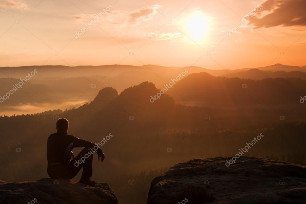 Tourist in black wind jacket sit on sharp rock and watch into colorful misty valley bellow. Sunny spring daybreak in rocky mountains.