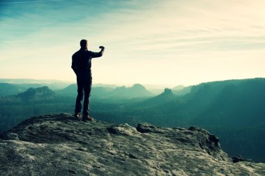 Tall hiker is taking photo by smart phone on the peak of mountain  at sunrise.