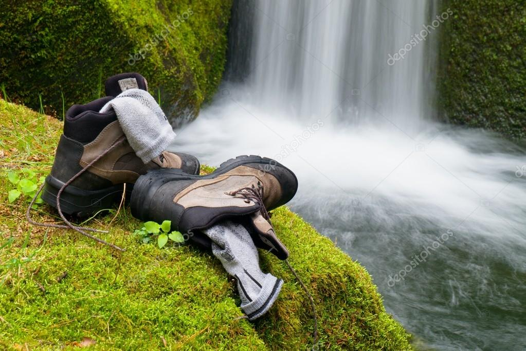Hiker high boots and sweaty grey socks. Resting on the mossy boulder at the  nice mountain stream