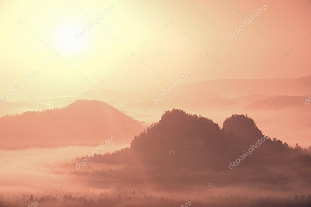 Misty landscape with fog between hills and orange sky within sunrise