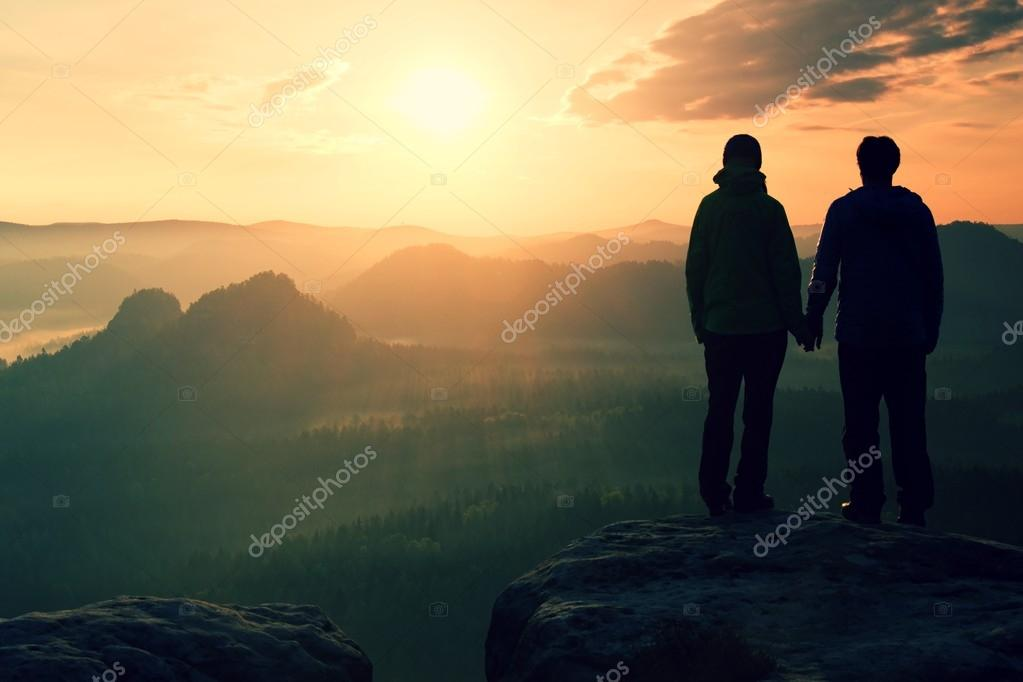 Young pair of hikers hand in hand on the peak of rock empires park and watch over the misty and foggy morning valley to Sun. Beautiful moment the miracle of nature