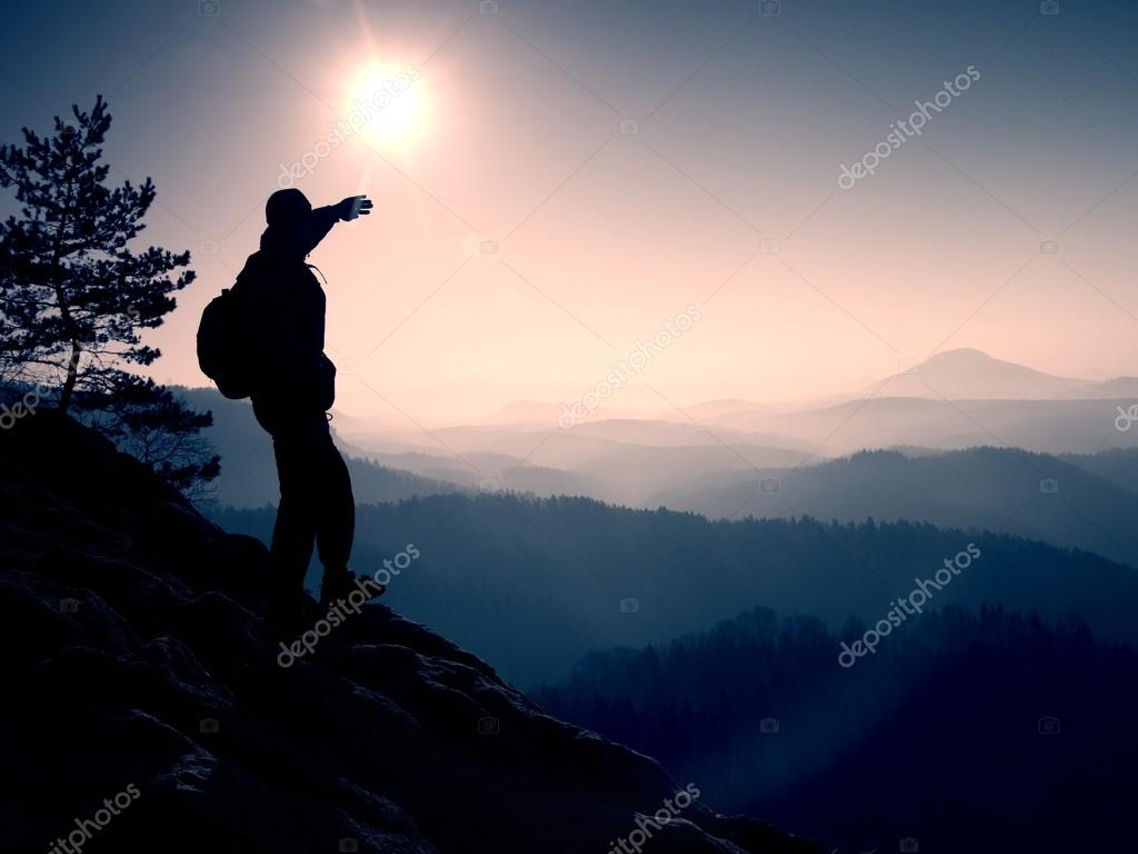 Sunny morning. Hiker is standing on the peak of rock in rock empires park and watch over misty and foggy morning valley