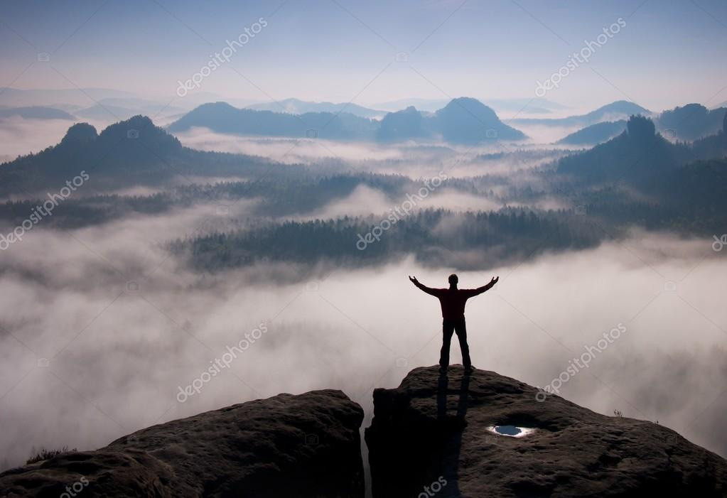 Gesture of triumph. Happy hiker in black.  Tall man on the peak of sandstone rock in national park Saxony Switzerland above valley