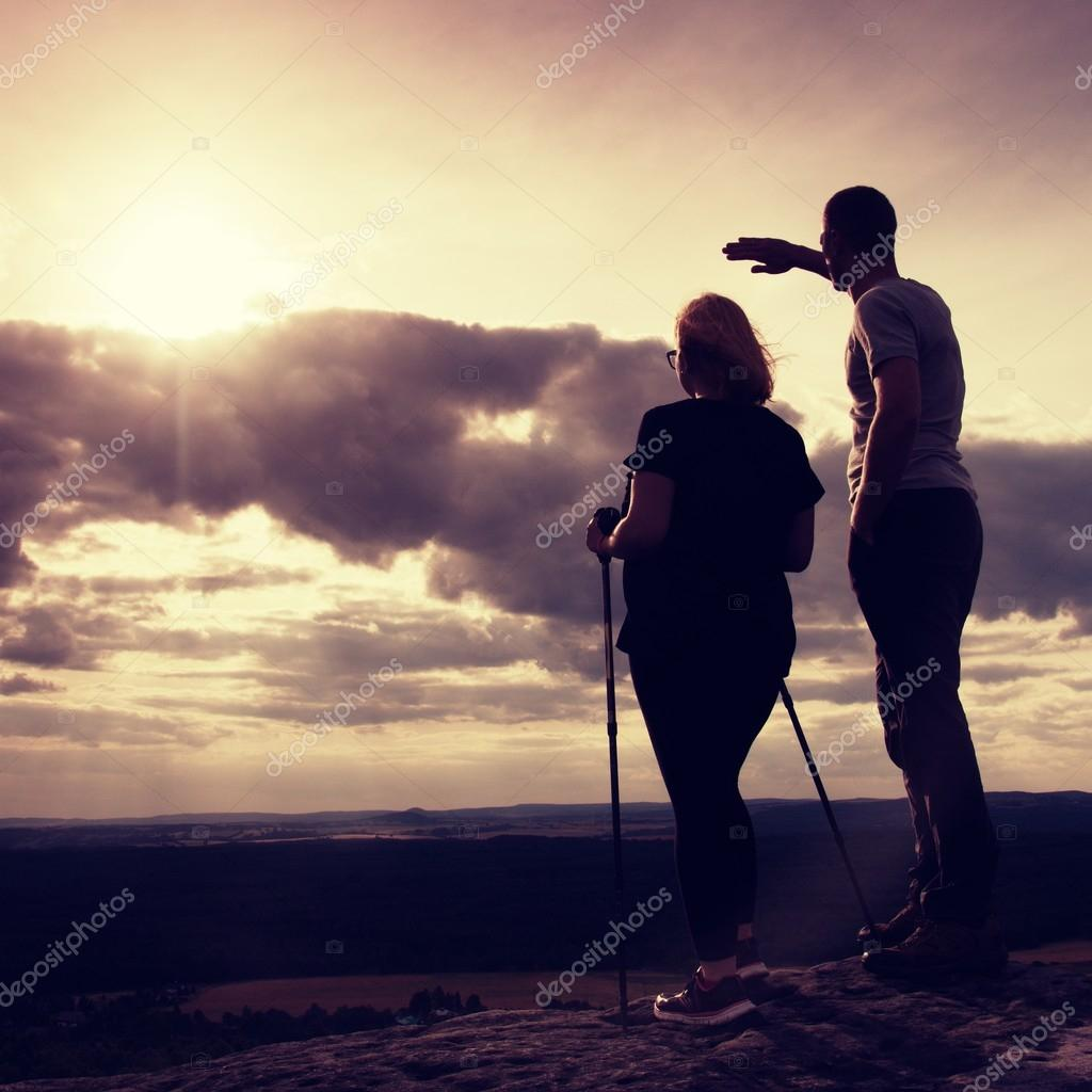 Couple enjoying marvellous moments during sunset . Young pair of hikers on the peak of rock watch  to Sun.