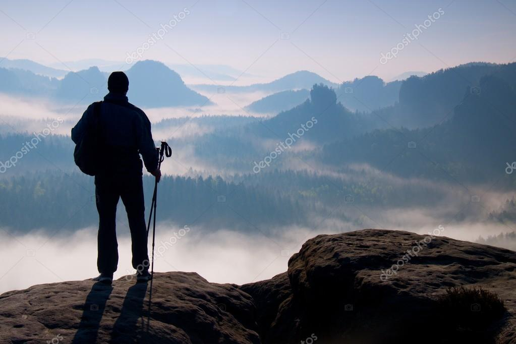 Dark silhouette of hiker with poles in hand. Sunny spring daybreak in rocky mountains. Hiker with sporty backpack stand on rocky peak  above valley.