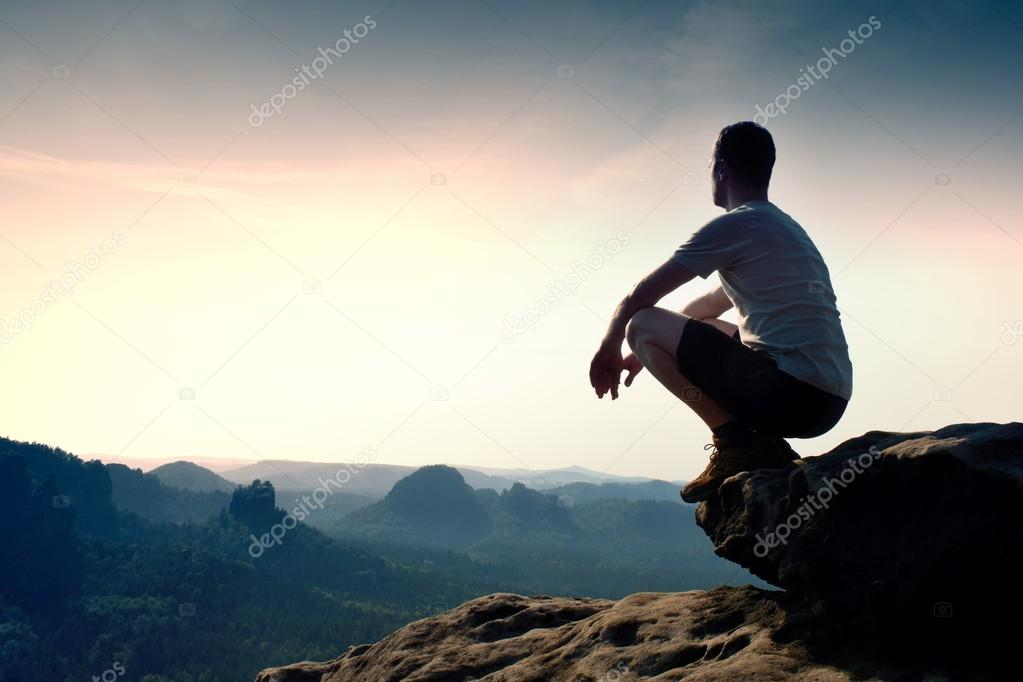 Young man in black sports pants and grey shirt  is sitting on cliff's edge and looking to misty valley bellow
