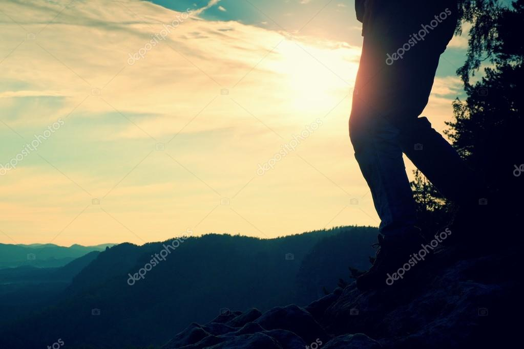 Woman hiker legs in tourist boots stand on mountain rocky peak. Sun n background