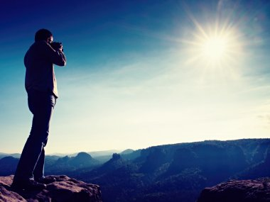 Professional photographer takes photos with mirror camera on cliff of rock. Dreamy misty landscape, hot Sun above