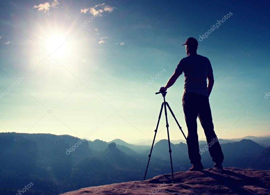 Professional photographer stay with tripod on cliff and thinking. Dreamy fogy landscape, blue misty sunrise in a beautiful valley below