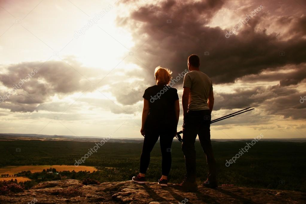 Couple enjoying marvellous moments during sunset . Young pair of hikers on the peak of rock watch over valley to Sun.