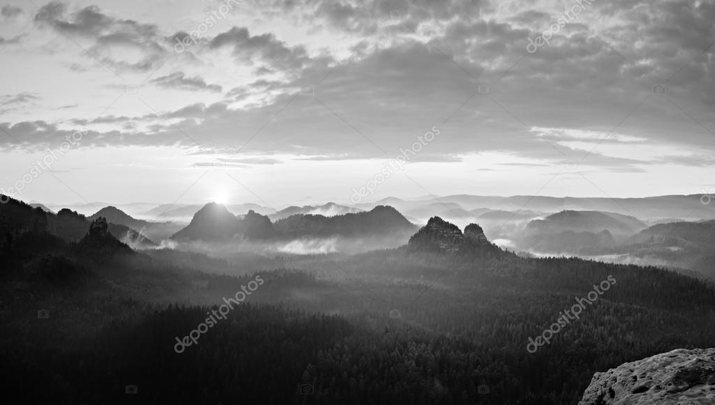 The deep misty valley in popular Saxony Switzerland park. Sharp peaks increased from foggy background. Black and white picture.