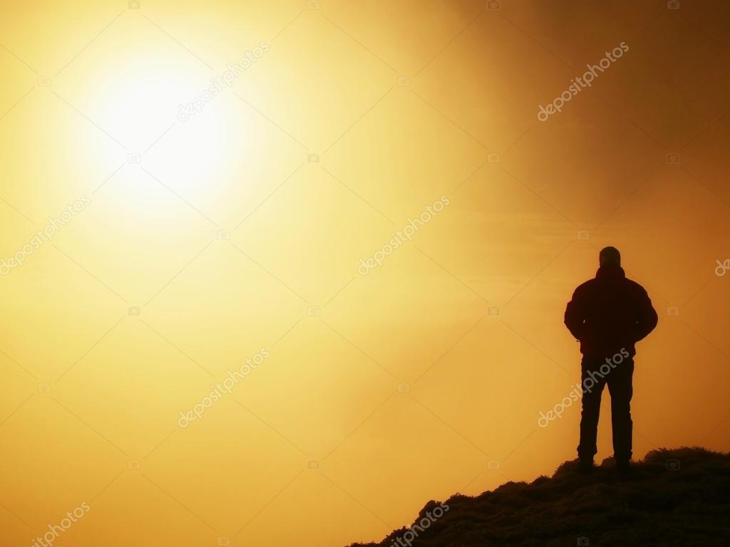 Tall adult hiker in black on the peak of the world . Heavy orange mist bellow in valley. Wonderful daybreak in mountains.
