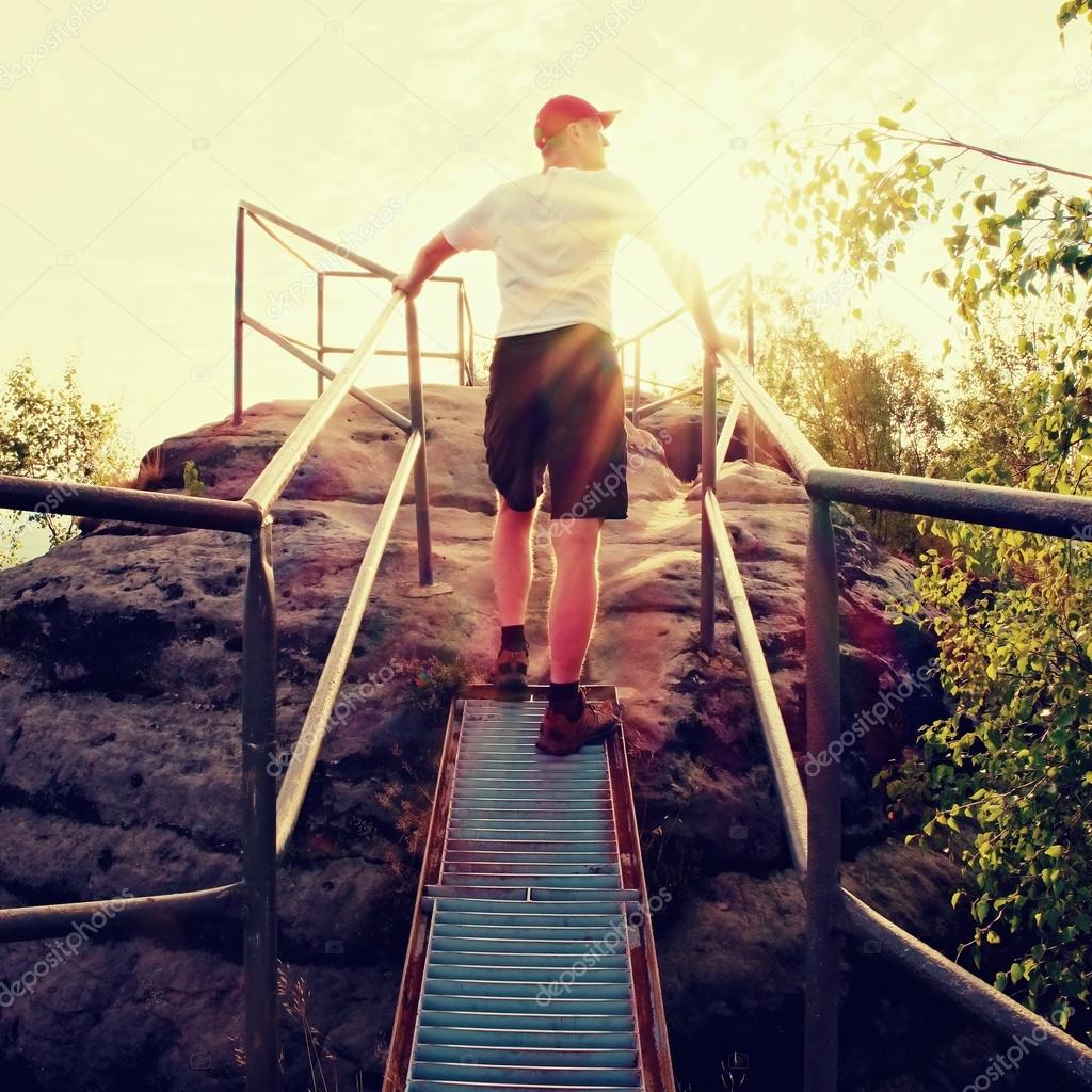 Tired hiker keep handrail on peak. Sunny spring daybreak in rocky mountains. Hiker with red baseball cap, dark pants and white shirt.