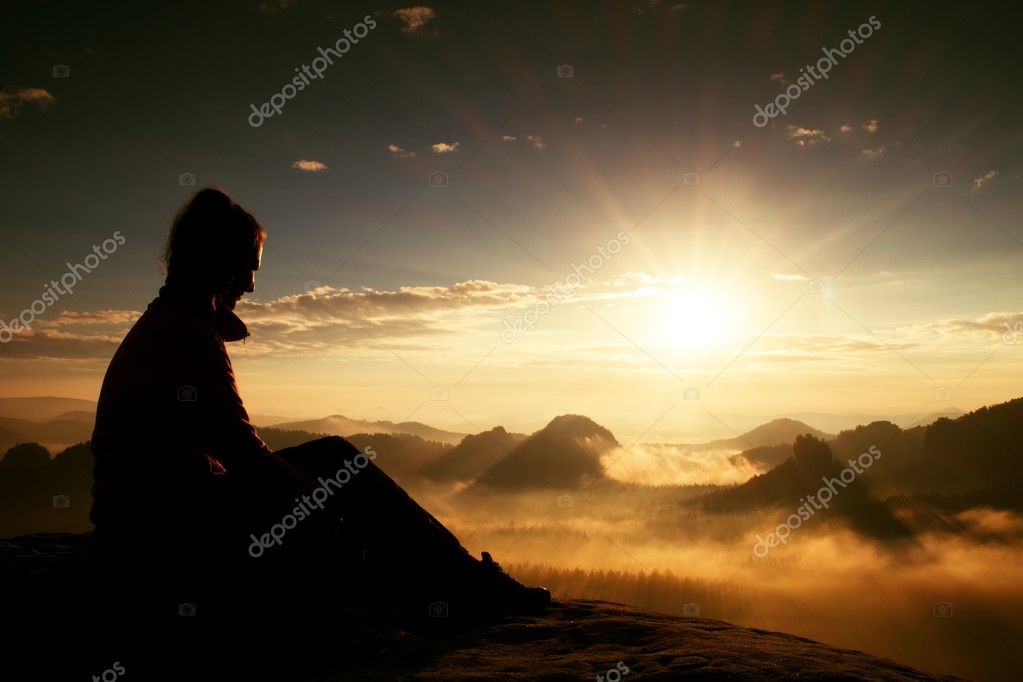 Beautiful  young long hair girl tourist enjoy daybreak on the sharp corner of sandstone rock and watch over valley to Sun.