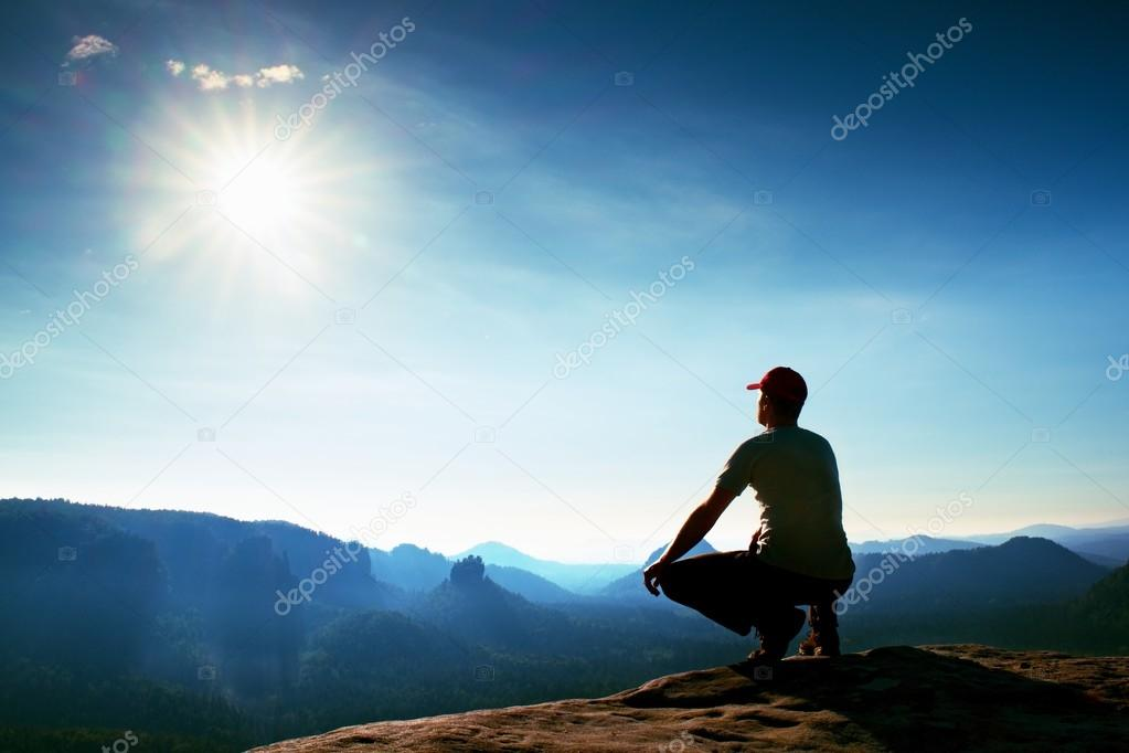 Runner in red cap and  in dark sportswear. Man sit  in squatting position on a rock in heather bushes, enjoy autumn scenery