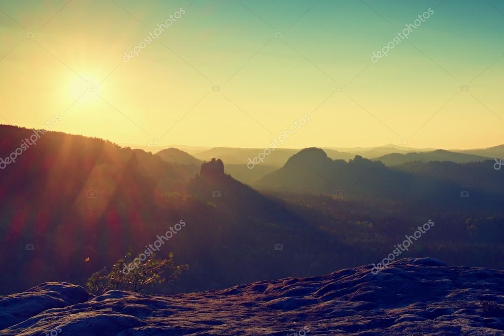 Sunny flares in lense. Colorful daybreak. Misty awakening in a beautiful hills. Peaks of hills are sticking out from foggy background